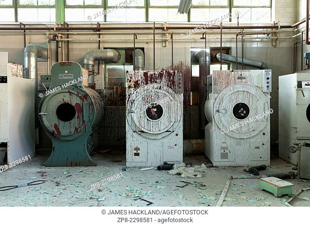 Industrial washers and dryers covered in red paint in an abandoned hospital. Ontario, Canada