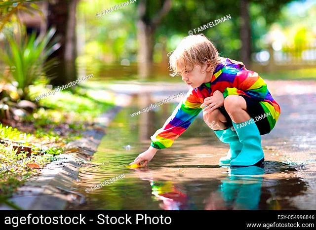 Kid playing in the rain in autumn park. Child jumping in muddy puddle on rainy fall day. Little boy in rain boots and red jacket outdoors in heavy shower