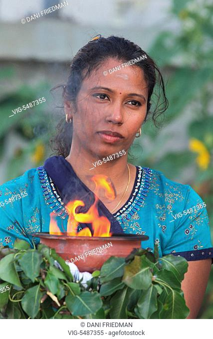 A female Tamil Hindu devotee holds a clay pot with burning camphor atop margosa leaves while escorting the large wooden chariot carrying the idol of Lord...