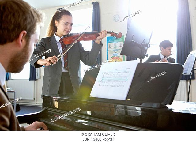 Middle school students and teacher playing musical instruments in music class