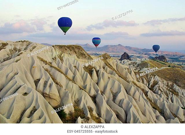 Hot air balloons flying over the peculiar geological formations of Cappadocia