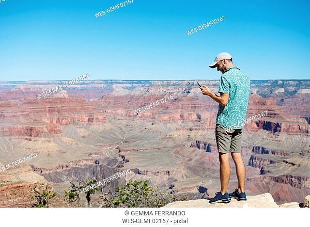 USA, Arizona, Grand Canyon National Park, Grand Canyon, man looking at smartphone