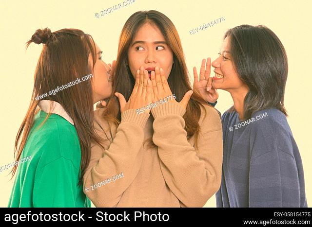 Studio shot of three young Asian women as friends together against white background