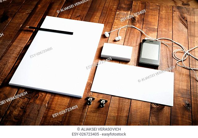 Photo of blank stationery. Template for branding identity. Blank letterhead, business cards, envelope, smartphone, headphones and pencil