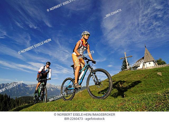 Mountain bikers at the Kraftalm alp, Wilder Kaiser massif at back, Mt Hohe Salve, Kitzbuehel Alps, Tyrol, Austria, Europe