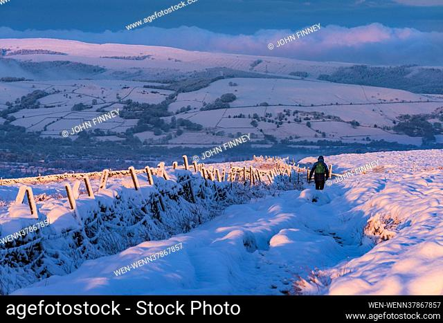 A stunning sunrise as walkers brave the cold conditions of the snow covered High Peak near Castleton in Derbyshire's Peak District Featuring: Spring snow across...