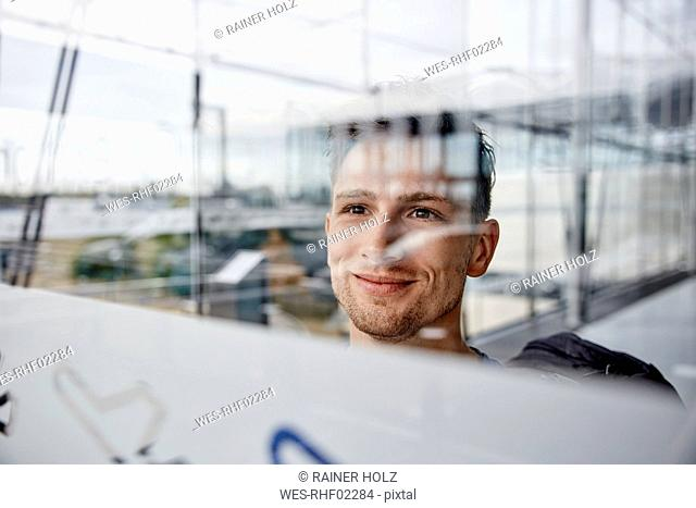 Portrait of smiling young man at the airport looking out of window