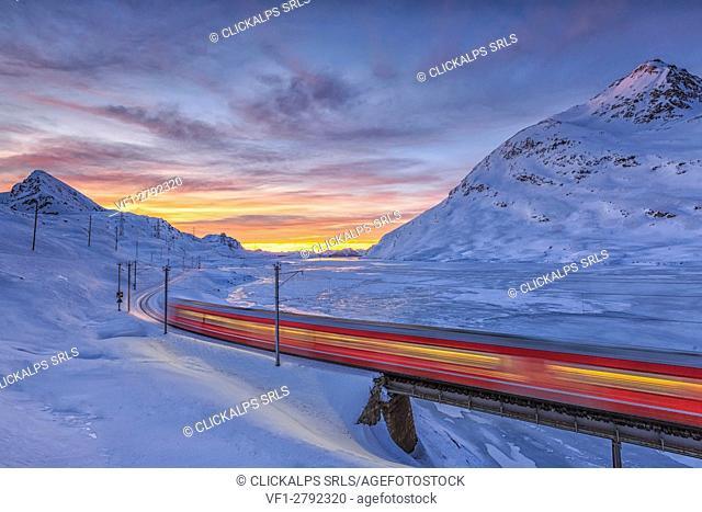 The Bernina Express passes on the shores of Lake Bianco completely frozen before the sun rises. Canton of Graubunden. Engadine. Switzerland. Europe