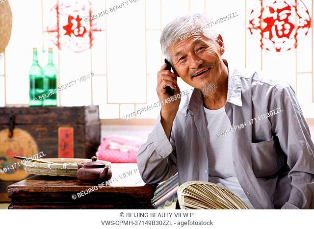 Elderly man talking on the phone