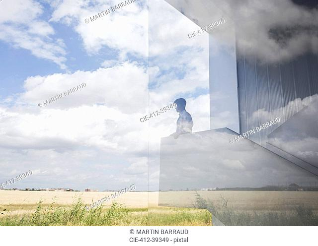 Pensive businessman on modern landing looking out window at sunny blue sky and clouds