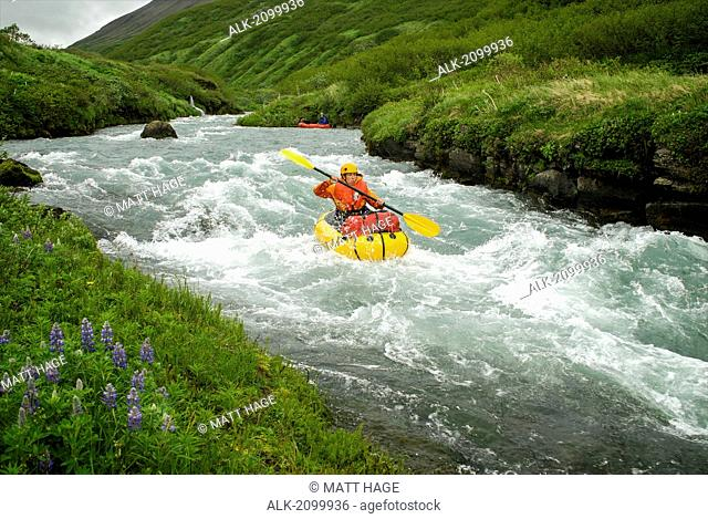 Woman Pack Rafts Down The Aniakchak River In Aniakchak National Monument And Preserve In Southwest Alaska