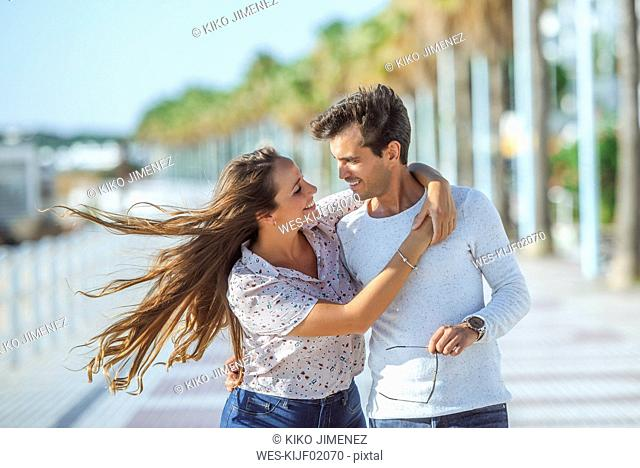 Happy young couple hugging on promenade