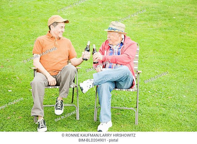 Older men drinking beer outdoors