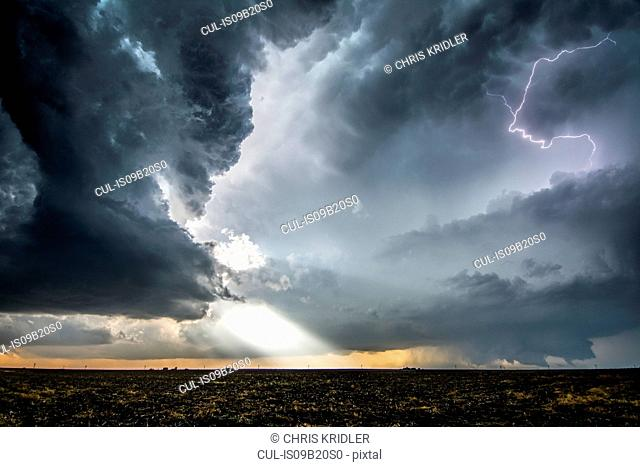 A supercell and tornado under the base of a storm, with beams of sunlight and lightning emerging from storm layers, Dodge City, Kansas