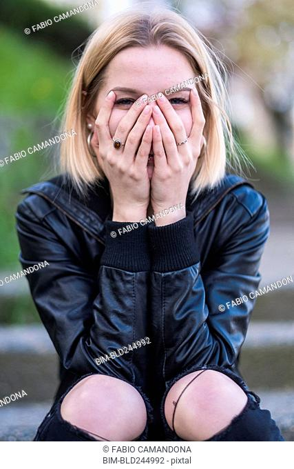 Laughing Caucasian woman covering face with hands