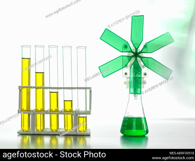Oil in test tubes by beaker with green turbine on table