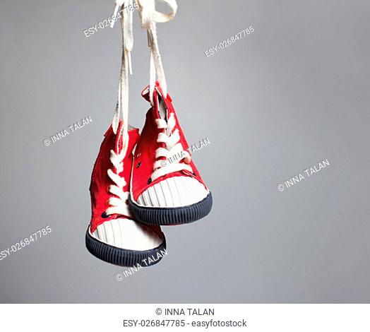 Sport baby shoes hanging on the gray background