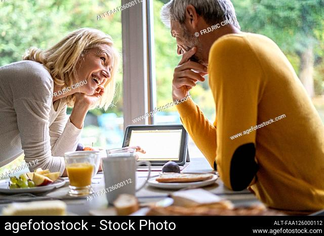 Smiling mature couple using digital tablet while having breakfast