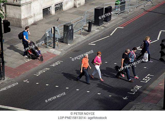 England, London, Waterloo. Pedestrians crossing traffic light controlled road crossing