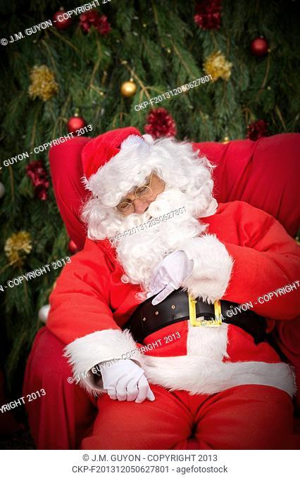 Sleeping Santa Clause on red Christmas armchair