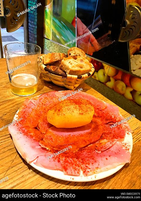 Lacon with potato and paprika and glass of cider. Asturias, Spain