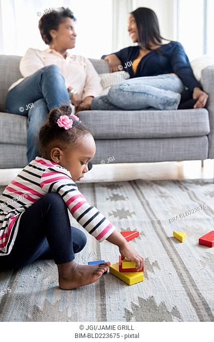 black baby girl playing on carpet with blocks