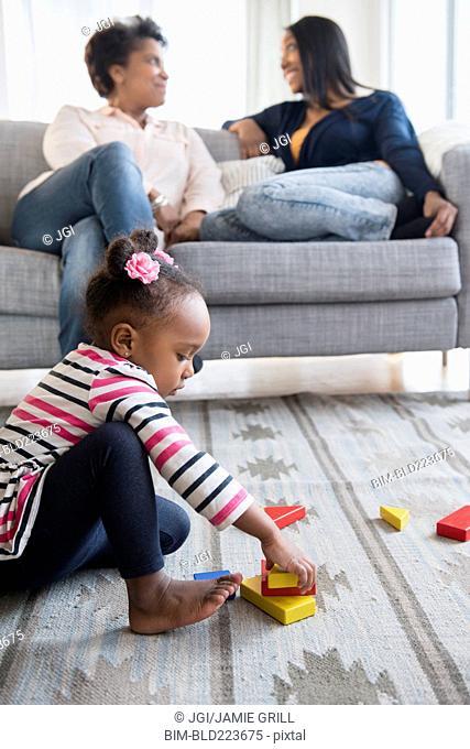 black baby girl playing on carpet with blocks