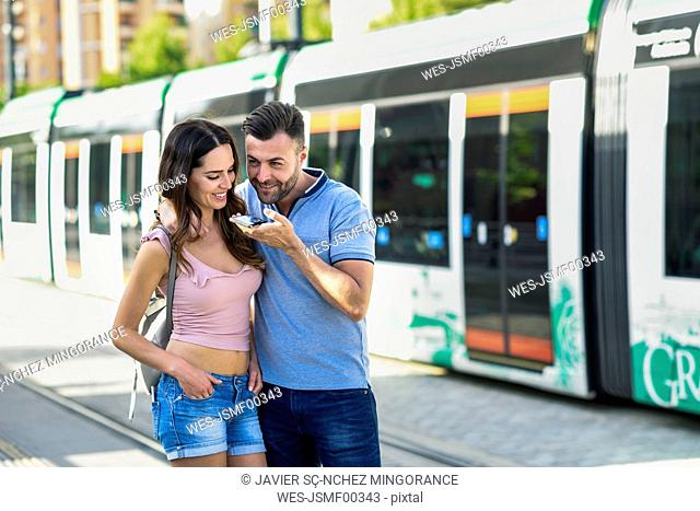 Couple using smartphone while waiting for tram at the station