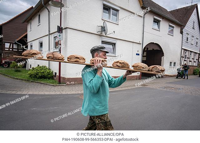 08 June 2019, Hessen, Sichertshausen: Manfred Will carries a board of freshly baked rye bread across a street in the middle of the village