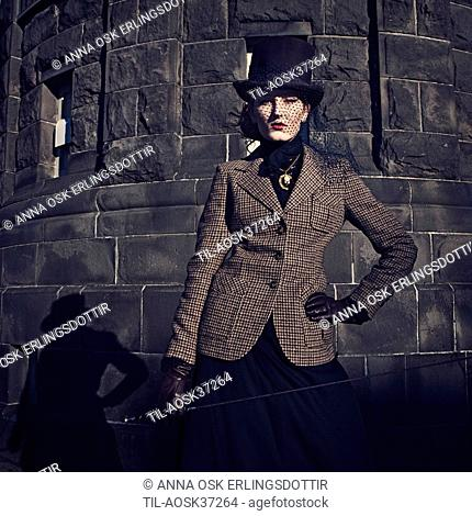 Female young adult in period clothing wearing black hat and veil with Harris tweed jacket and gloves holding riding crop looking at camera
