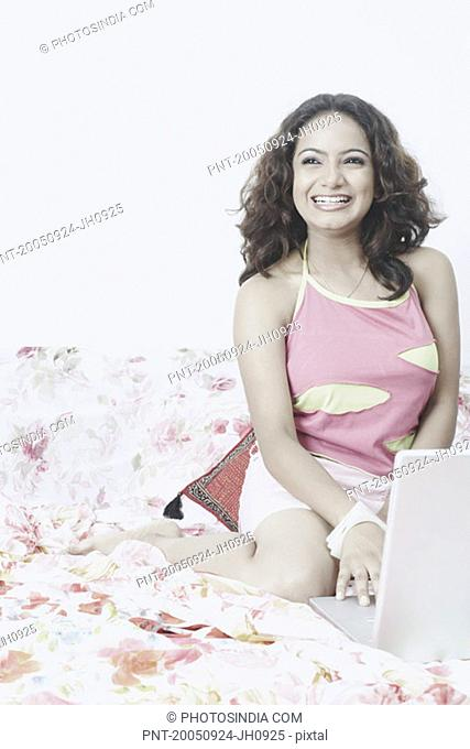 Young woman sitting on the bed using a laptop