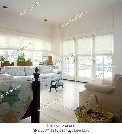 BEDROOMS: Light and Airy bedroom, view towards windows with white fabric shades. Wood floor. Sofa seating area, partial view of bed on left
