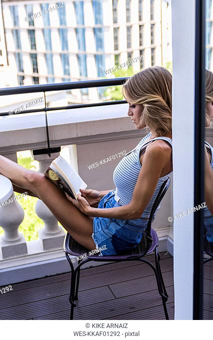 Blond woman sitting on balcony, reading book