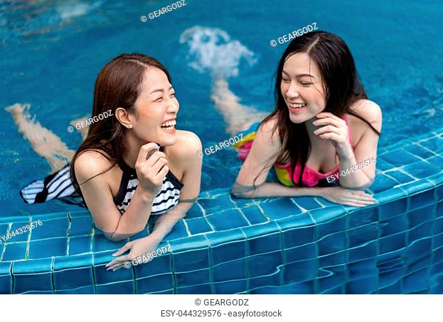 two young women friends enjoy in the swimming pool