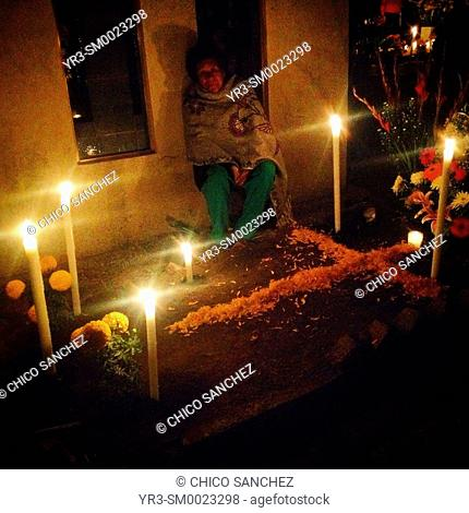 A woman sits by a tomb decorated with candles during Day of the Dead celebrations in the cemetery of San Gregorio Atlapulco, Xochimilco, Mexico City, Mexico