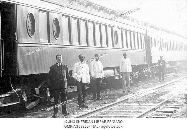 African American train employees are standing next to a white train employee in front of a train, the African American men are wearing light colored shirts and...