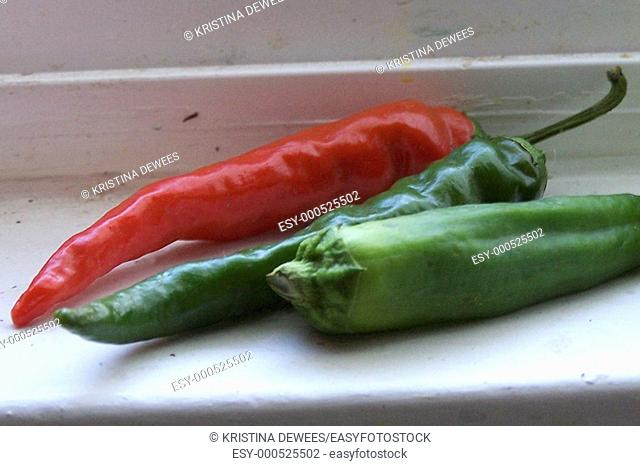 Some long slim red cayenne peppers ripening on a white windowledge
