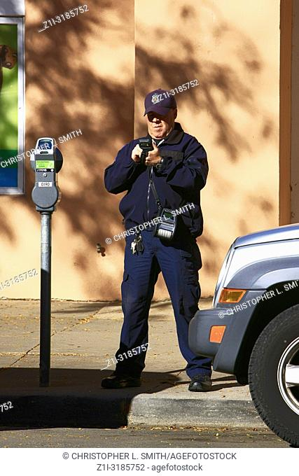 A male parking enforcement officer digitally writes a ticket for a vehicle whose parking time has elaspsed in downtown Santa Fe NM, USA