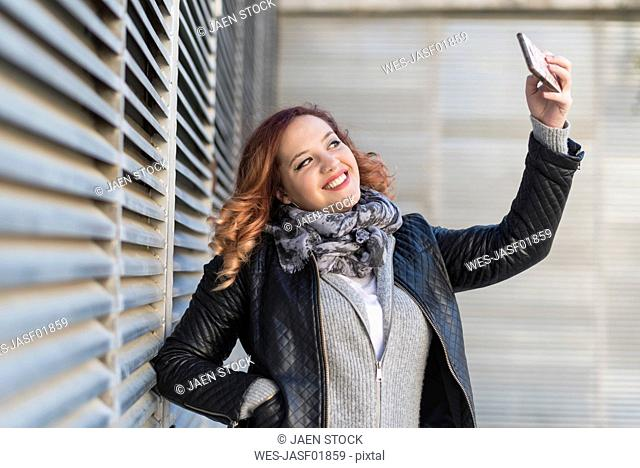 Portrait of happy young woman taking selfie with smartphone