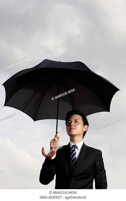 Man holding an umbrella looking worried