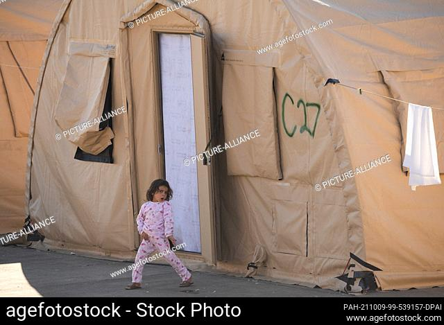 09 October 2021, Rhineland-Palatinate, Ramstein: A little girl from Afghanistan dances in front of a tent in which she has taken shelter with her family at the...