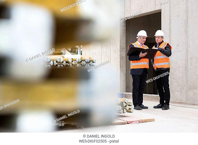 Two men wearing safety vests talking on construction site