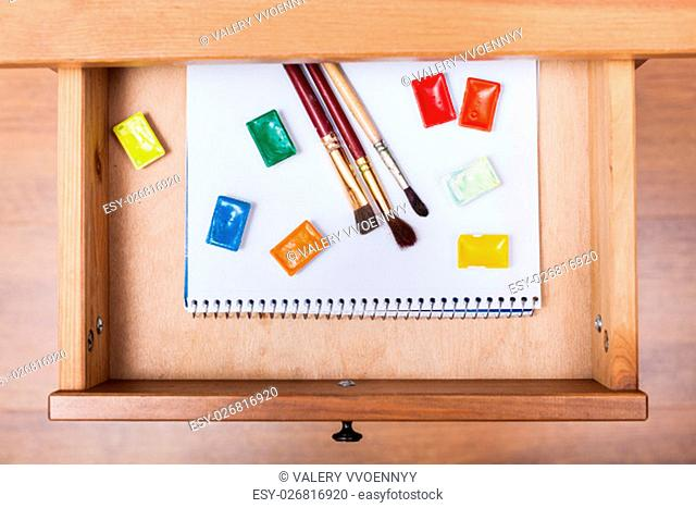 above view of paint brushes and water paints on album in open drawer of nightstand