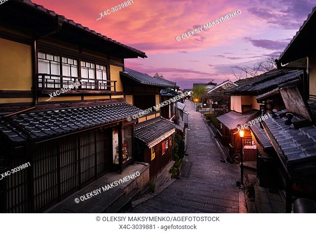 Beautiful sunrise scenery of Yasaka dori historic street in Kyoto empty and quiet in early morning with colorful dramatic red purple sky and shining street...