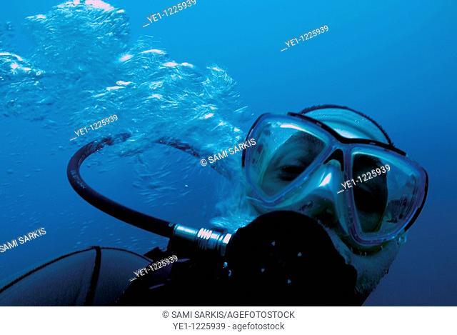 One scuba diver blowing bubbles underwater, Marseille, France