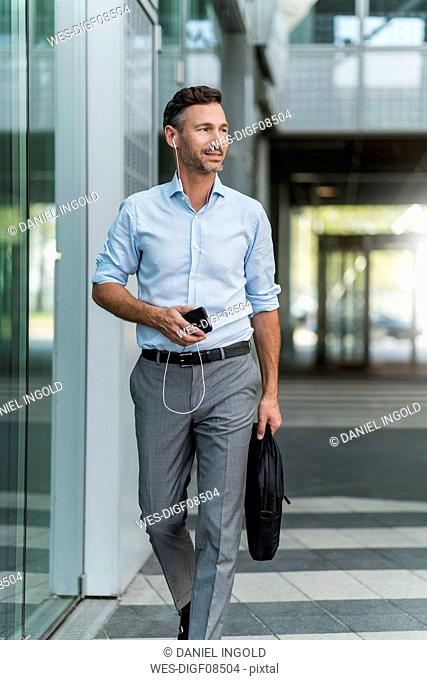 Businessman with cell phone and earphones on the go
