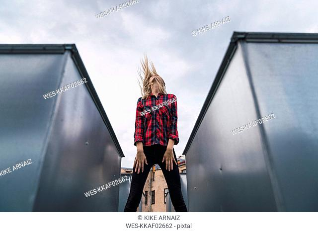 Fashionable young woman on rooftop tossing her hair