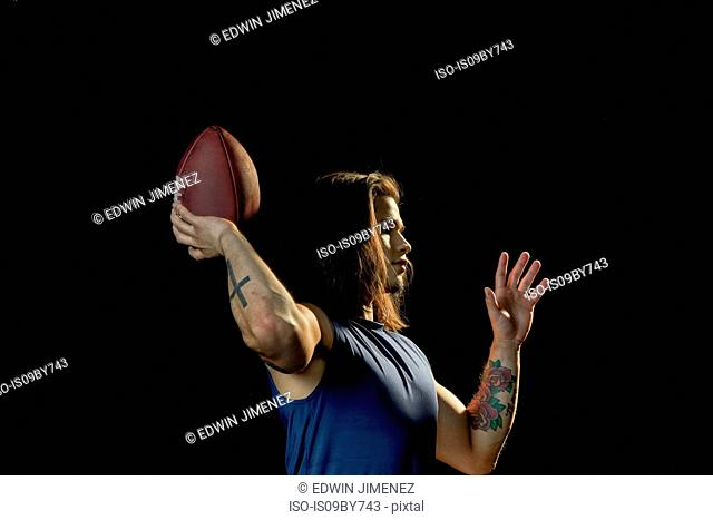 Portrait of football player with football, black background