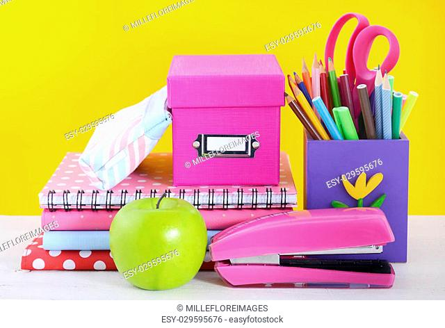 Back to School or Education Concept with classroom desk and bright colored stationery supplies on white wood rustic table and fun yellow background