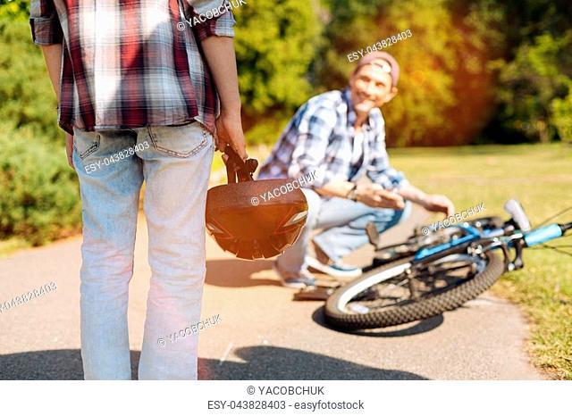 It wont take long. Trained skillful attentive dad stopping on the side of a road for repairing the bicycle his son riding